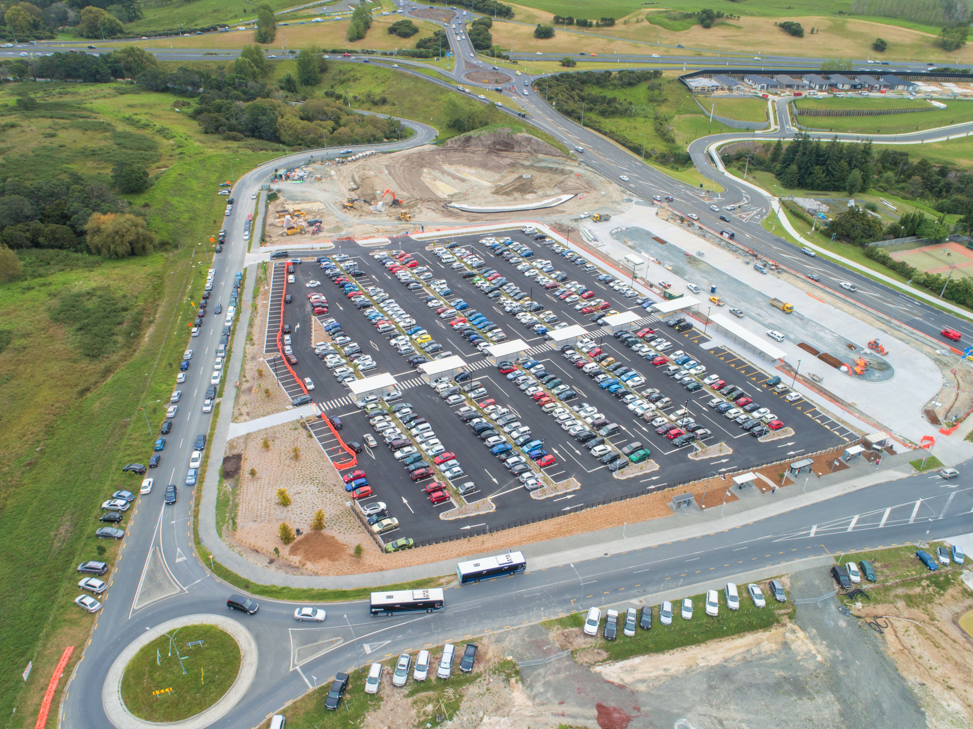 Overhead photo of a carpark full of cars with engineering construction in the background